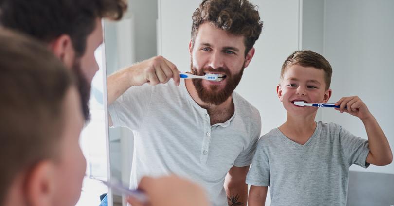 Pai e filho escovando os dentes em frente ao espelho